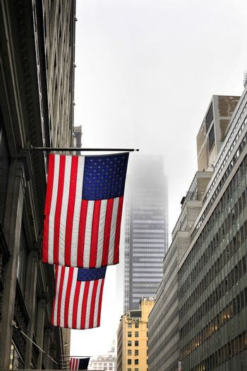 New York, NY, USA - American flags on a pole, fluttering in the wind, on the facade of a building on a foggy day