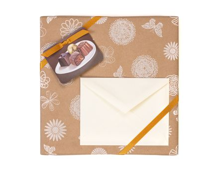 Gift wrapped box with chocolate candies and golden tape on a white background with copy space envelope.