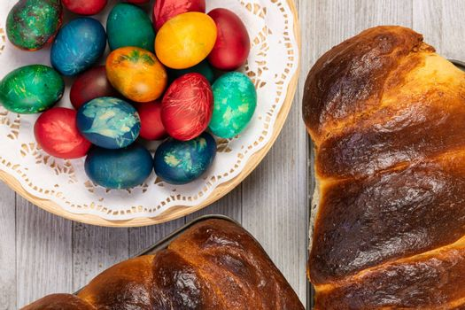 Traditional sweet bread in baking pan and Easter painted eggs, top view.