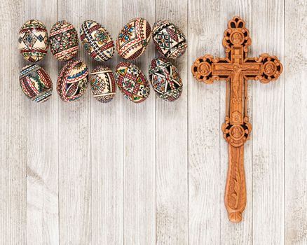 Painted wooden eggs traditional of Eastern Europe with delicately sculpted wooden cross and copy space.