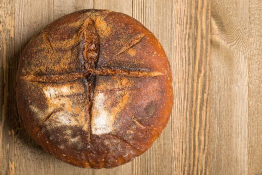 Homemade sourdough bread made in traditional style during Easter or other Christian Holidays with a simple cross signifying that bread is the body of Christ with copy space.