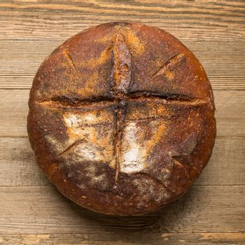 Homemade sourdough bread made in traditional style during Easter or other Christian Holidays with a simple cross signifying that bread is the body of Christ.