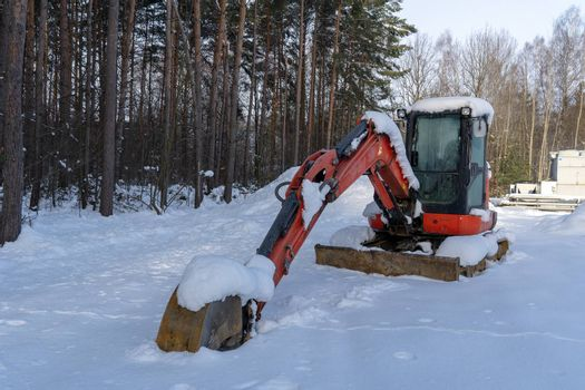 A red excavator near a forest is covered by snow, as the construction site is sitting idle due to the low temperature, snow and ice.