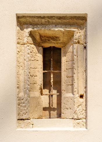 An ancient stone window with a rusty window grid inside the inner courtyard of the Stadtschloss Dresden in Germany on a very sunny day.
