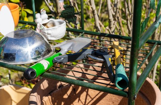 Gardening tools sitting on an outdoor shelf in a garden waiting to be used to cultivate plants.