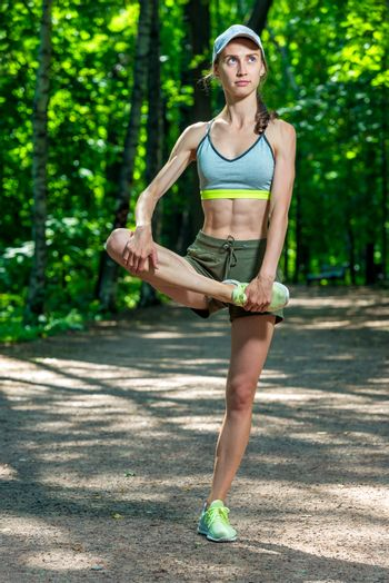 beautiful muscular athletic girl warms up her muscles before jog