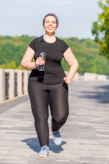 girl plus size with a bottle of water during a morning jog in th