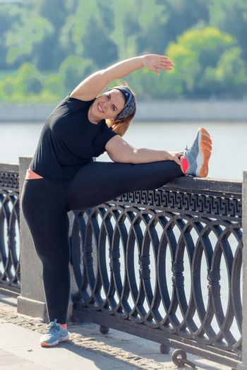 very flexible stout woman performs exercises on the embankment i