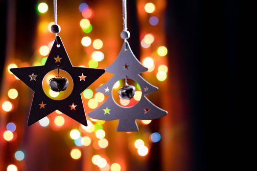 Handmade christmas decorations, star and fir tree with small round bells on dark background with colorful bokeh lights