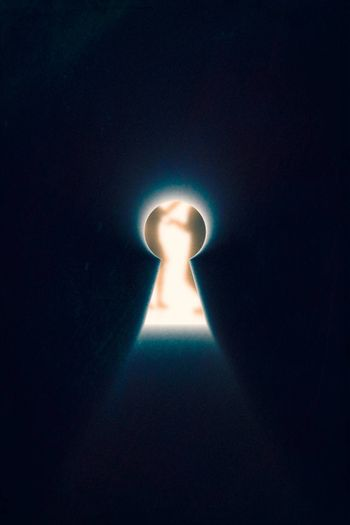 Keyhole with rays of bright light from it on dark blue background. Through keyhole talking man and woman can be seen.