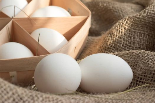 Close-up view of white chicken eggs in ecological packaging with hay or straw on sackcloth in a rustic style