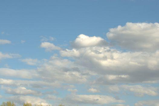 White cumulus clouds against a blue sky.