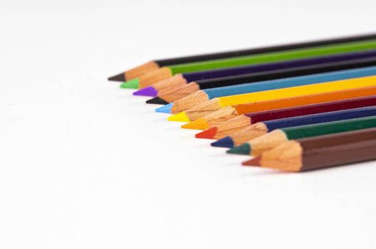 A group of colored pencils is shown with selective focus on center pencils.