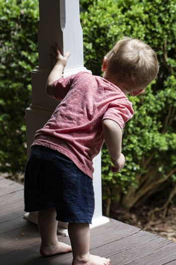 Barefoot male toddler peers around post on wooden porch.