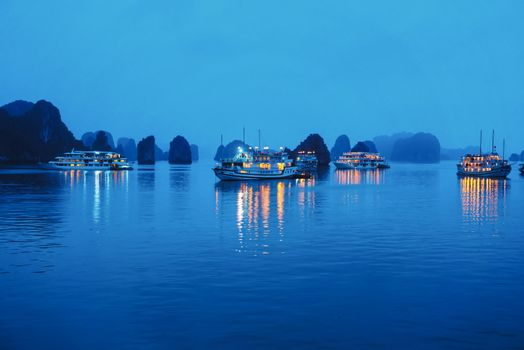 Ha Long bay at night with cruise ship lamps and limestone rocks reflections