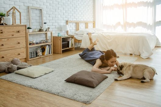 Asian girl playing with dog in the morning.A girl is parodying his pet.Warm tone.Do not focus on objects.