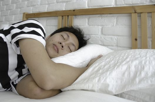Asian guy sleeping in a white bedroom.Man sleeps well in bed in a white bedroom. Relax in the room.