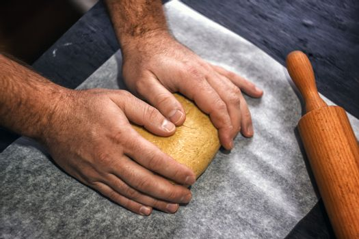 man's hands knead the dough in retro style on a dark background