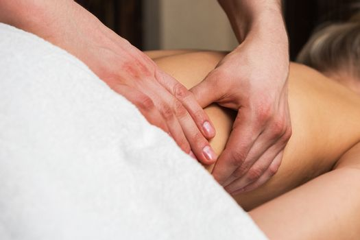 Close-up masseur hands doing back massage to woman in spa center.