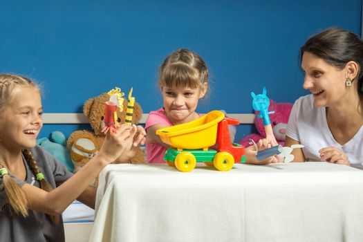 Mom plays with two daughters in a self-made finger puppet theater
