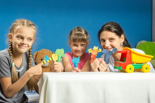 Mom with two daughters playing in a makeshift finger puppet theater