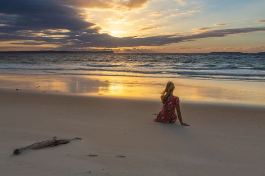 Female sitting on the sand watching the sunrise