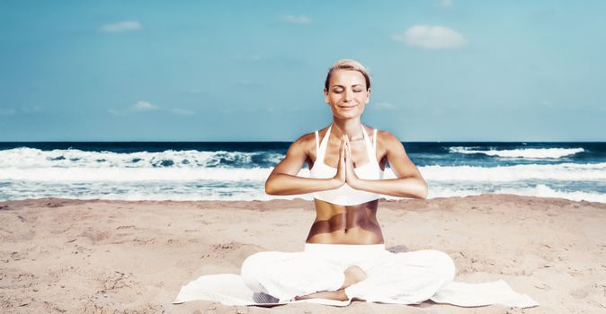Pretty woman doing yoga exercise on the beach, sitting on the sand near the sea in lotus pose and meditating with closed eyes, happy healthy summer vacation