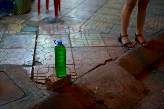 PET bottle full of gasoline for sale placed on top of a pavement on the sidewalk in Vietnam at night.
