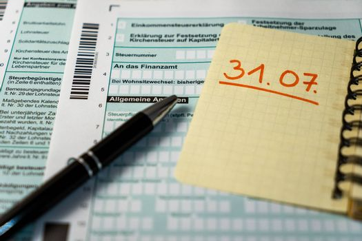 German tax declaration form with a black pen in foreground and a yellow paper indicating the deadline of the 31st of july.