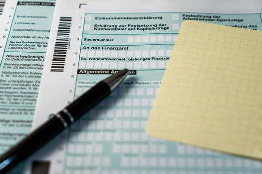 German tax declaration form with a black pen in foreground and a yellow paper with enough space to fill out.