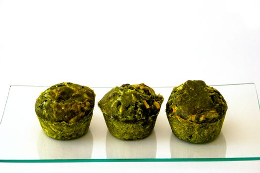 three green cakes on a glass tray and  white background