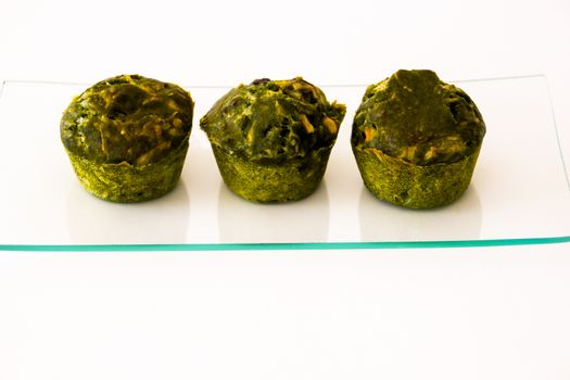 three green cakes on a glass tray with white background