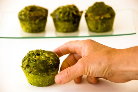 Three green muffins on a glass tray at the background and a hand catching another one at the foreground