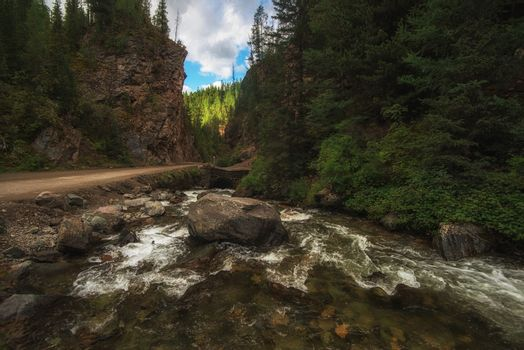 Mountain river, and road punched through the rocks in the Altai mountains, Siberia Russia