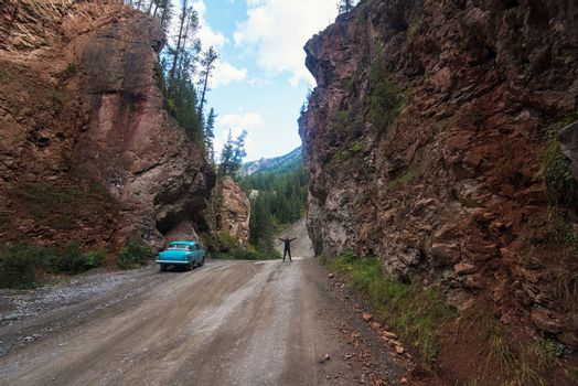 Woman and car on the road punched through the rocks in the Altai mountains, Siberia Russia