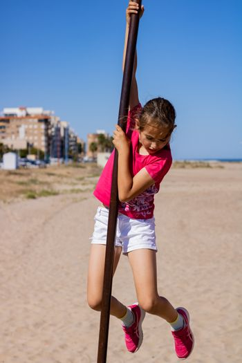 Little girl playing in a playground on the beach