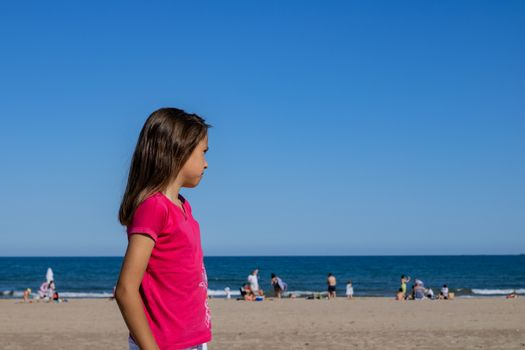 Little girl posing on the beach with the Mediterranean Sea in the background
