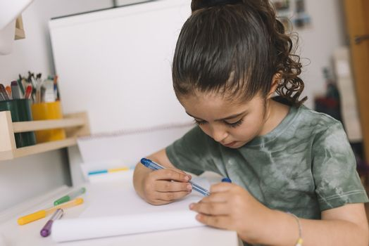 little girl draws at home with colored markers, she is drawing on the desk in her room