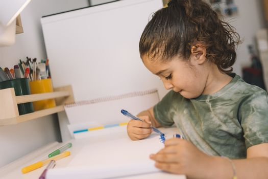 little girl drawing at home with colored markers, she is drawing on the desk in her room