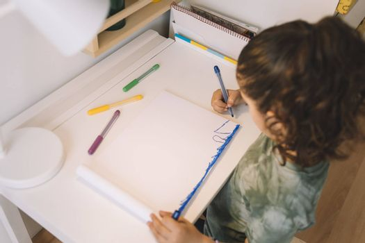little girl draws at home with color markers, she is drawing on the table in her room