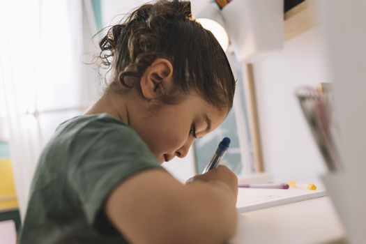little girl draws concentrated at home with color markers, she is writing on the table in her room