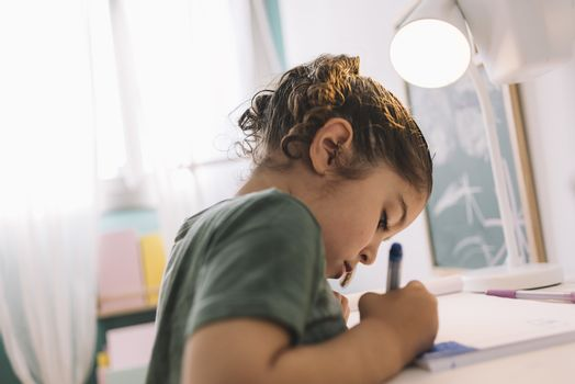 little girl draws concentrated at home with color markers, she is drawing on the desk in her room