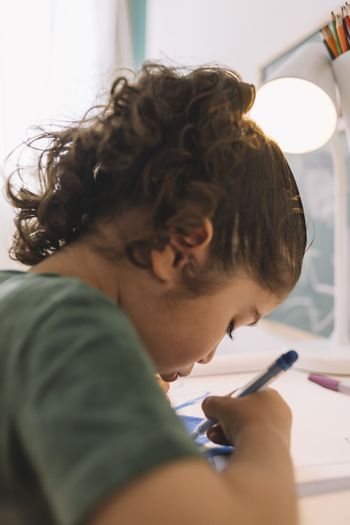 vertical photo of a little girl drawing concentrated at home with color marker, she is drawing on the table in her room