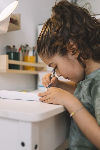 vertical photo of a little girl that writes concentrated at home with a color marker, she is drawing on the table in her room