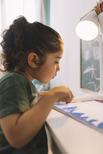 vertical photo of a little girl drawing concentrated at home with a color marker, she is drawing on the table in her room