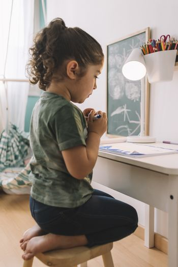 vertical photo of a little girl that draws concentrated at home with color markers, she is drawing on the table in her room