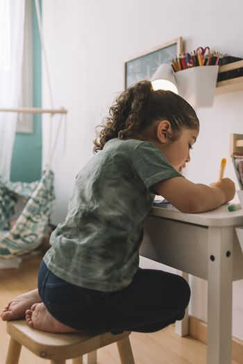 vertical photo of a little girl that draws concentrated at home with color markers, she is drawing on the desk in her room