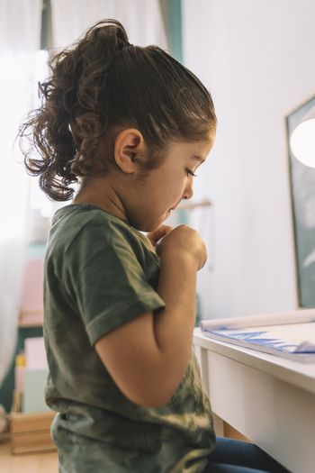 vertical photo of a little girl looking at the draw she just made at home with color markers, the draw is on the desk in her room