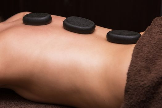 Woman receiving a therapy with hot stones in spa center, closeup photo