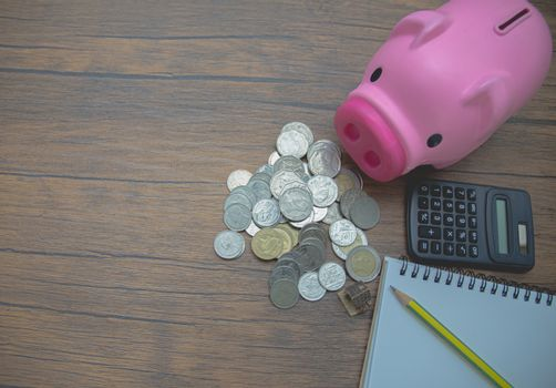 Coin, piggy bank and pencil set on brown table.Black calculator on brown background.